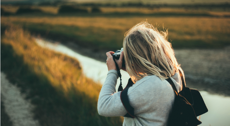 Woman shooting landscape scene with DSLR camera