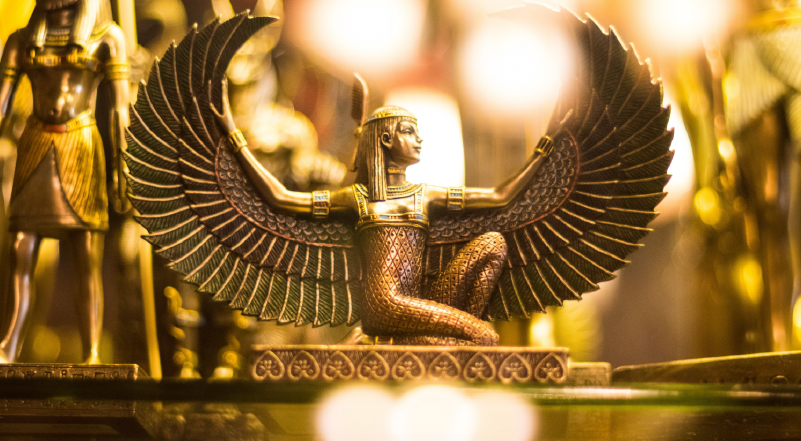 Photo of golden Egyptian statue of winged woman